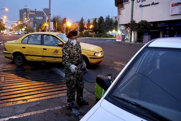 A Revolutionary Guard member disinfects a car to help prevent the spread of the new coronavirus in downtown Tehran, Iran, Wednesday, March 25, 2020. (AP Photo/Ebrahim Noroozi)