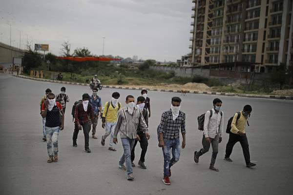 A group of Indian daily wage laborers walk along an expressway hoping to reach their homes, hundreds of miles away, as the city comes under lockdown in Ghaziabad, on the outskirts of New Delhi, India, Thursday, March 26, 2020. (AP Photo/Altaf Qadri)