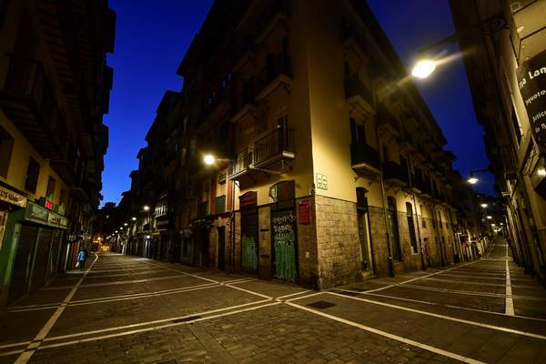 A pedestrian walks near to the corner between Estafeta, left, and Javier street of the old city, in Pamplona, northern Spain, Wednesday, March 25, 2020. (AP Photo/Alvaro Barrientos)