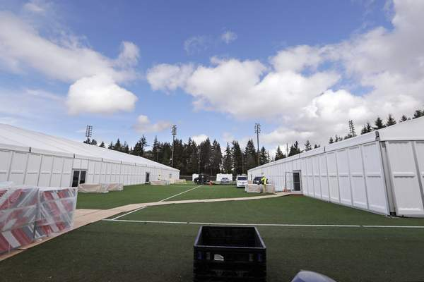 In this photo taken Tuesday, March 24, 2020, two massive temporary buildings meant for use as a field hospital for coronavirus patients stand together on a soccer field in the Seattle suburb of Shoreline, Wash. (AP Photo/Elaine Thompson)