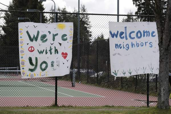 In this photo taken Tuesday, March 24, 2020, handmade signs posted to a tennis court fence are set to greet future patients at a temporary field hospital for coronavirus patients on an adjacent soccer field in the Seattle suburb of Shoreline, Wash. (AP Photo/Elaine Thompson)