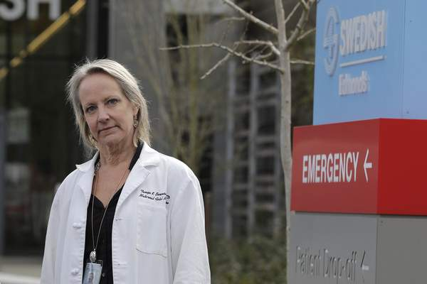 In this Tuesday, March 24, 2020, photo, Dr. Tanya Sorensen, a practicing maternal fetal medicine physician at Swedish Medical Center, and executive director for women's services, poses in Edmonds, Wash., north of Seattle. Several dozen expectant moms who had planned to give birth at the birth unit of the center will now have to go elsewhere because the facility is being repurposed to treat victims of the new coronavirus. (AP Photo/Ted S. Warren)