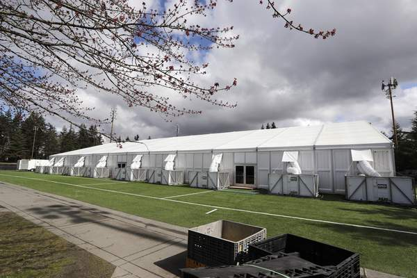 In this photo taken Tuesday, March 24, 2020, one of a pair of massive temporary buildings meant for use as a field hospital for coronavirus patients stands on a soccer field in the Seattle suburb of Shoreline, Wash. (AP Photo/Elaine Thompson)