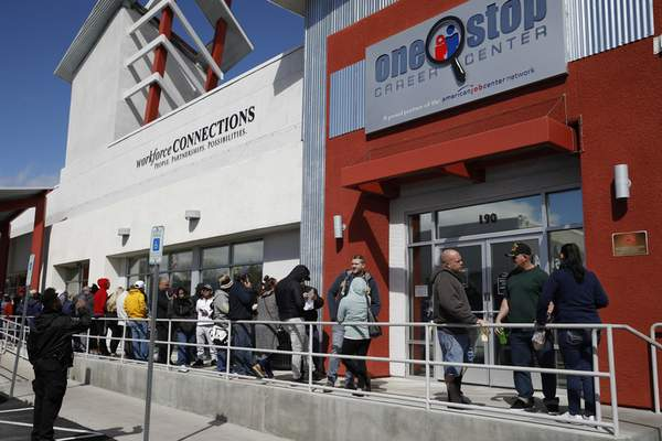 FILE - In this March 17, 2020 file photo, people wait in line for help with unemployment benefits at the One-Stop Career Center in Las Vegas. (AP Photo/John Locher, File)