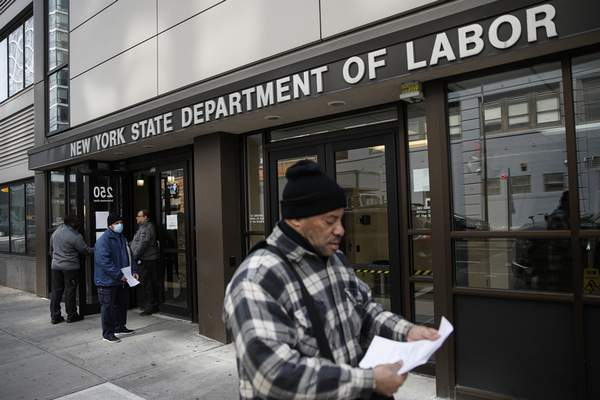 FILE - In this March 18, 2020 file photo, visitors to the Department of Labor are turned away at the door by personnel due to closures over coronavirus concerns in New York. (AP Photo/John Minchillo, File)