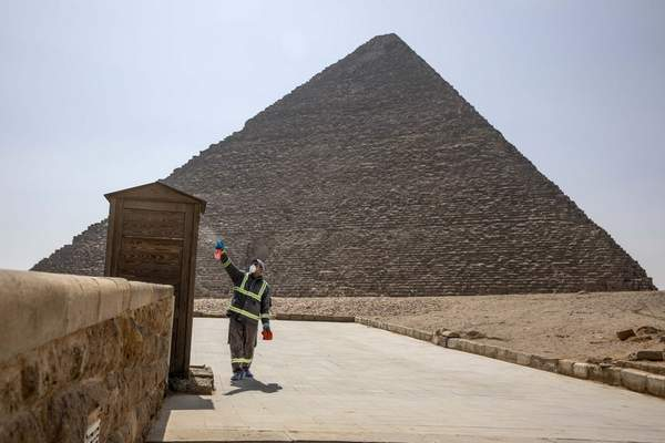 Municipal workers sanitize the areas surrounding the Giza pyramids complex in hopes of curbing the coronavirus outbreak in Egypt, Wednesday, March 25, 2020. (AP Photo/Nariman El-Mofty)