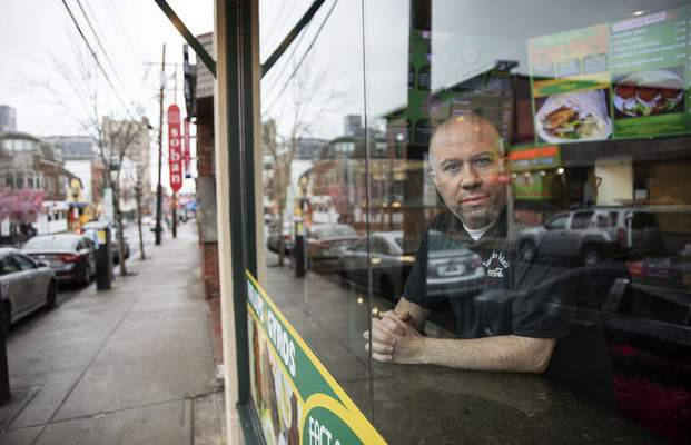 Paul Boutros, owner of East Side Pockets, a small restaurant near Brown University, looks out onto an empty street since students were sent home two weeks ago, Wednesday, March 25, 2020, in Providence, R.I. (AP Photo/David Goldman)
