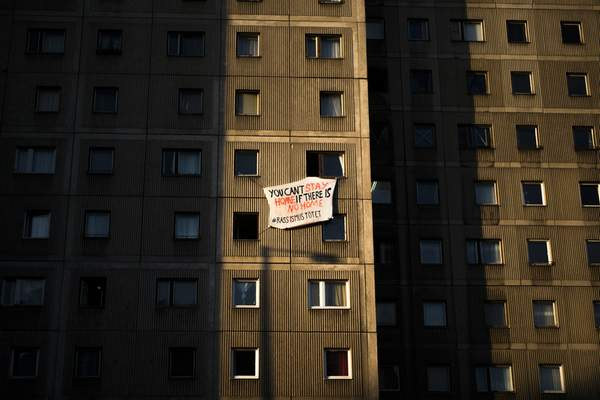 A poster supporting homeless people and refugees is displayed at an apartment building in central Berlin, Germany, Wednesday, March 25, 2020. (AP Photo/Markus Schreiber)