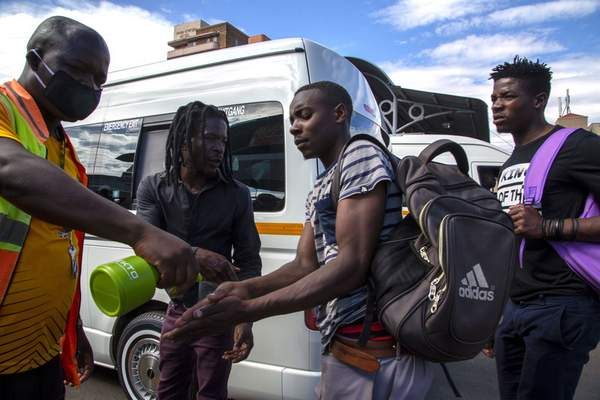 Associated Press A taxi marshal wearing a face mask sprays sanitizer to passengers to protect against coronavirus Thursday in Johannesburg, South Africa, just hours before the nation went into lockdown.