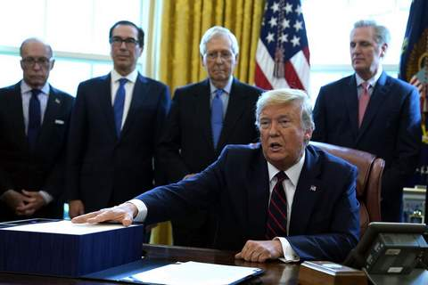 President Donald Trump speaks before he signs the coronavirus stimulus relief package in the Oval Office at the White House, Friday, March 27, 2020, in Washington. (AP Photo/Evan Vucci)