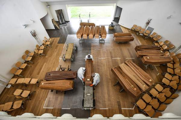 Associated Press photos Coffins for coronavirus victims are collected after delivery by a military truck Friday at a cemetery near Milan, Italy. The coronavirus has killed more than 9,000 people in Italy.