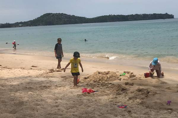 Associated Press photos Tourists play on a beach in Phuket, Thailand, on Thursday. Thousands of tourists all across Asia arfacing unprecented restrictions because of the virus, frantically trying to get back home.
