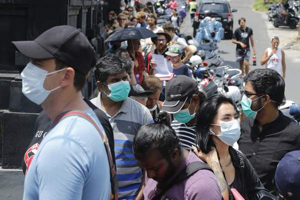 Foreign tourists  unable to fly home because of the pandemic  line up this week outside an immigration office to extend their visas in Bali, Indonesia.