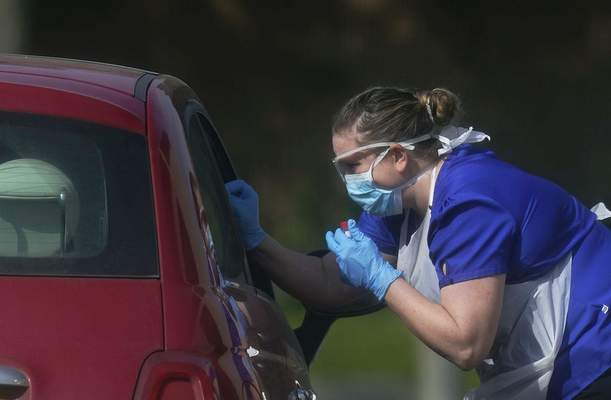 A NHS worker is tested for coronavirus at a temporary drive through testing station in the car park of Chessington World of Adventures in Chessington, England, Saturday March 28, 2020.