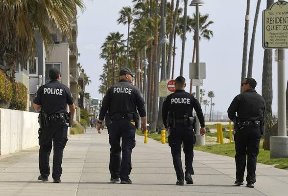 Associated Press Los Angeles police officers patrol a sparsely populated Venice Beach boardwalk Saturday in Los Angeles.
