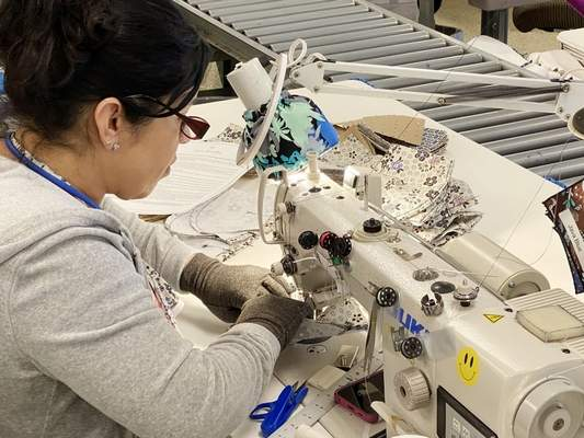 A Vera Bradley worker sews masks for possible use by hospital patients and visitors. The company is trying to access material suitable to sew medical-grade face masks, too.  Courtesy photo  (worker's name was requested but not provided)