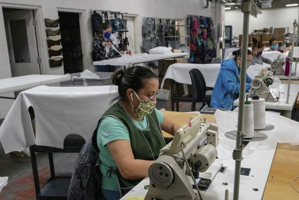 Laticia Romero, foreground, sews personal protective equipment for handbag maker Cinda B. The local company is providing face masks, gowns and face shields to health care workers.  Courtesy photo
