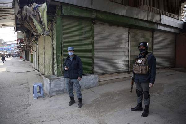 Police officers guard shuttered storefronts following a lockdown amid concern over spread of coronavirus in Kabul, Afghanistan, Sunday, March 29, 2020. (AP Photo/Rahmat Gul)