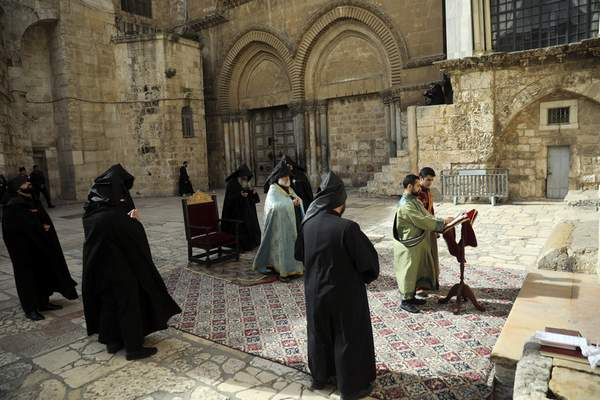 Arminian orthodox priests hold a mass outside closed Church of the Holy Sepulchre, where Christians believe Jesus Christ was buried, in Jerusalem, Saturday, March 28, 2020, as Israel tightens measures to fight the spread of the coronavirus. (AP Photo/Mahmoud Illean)