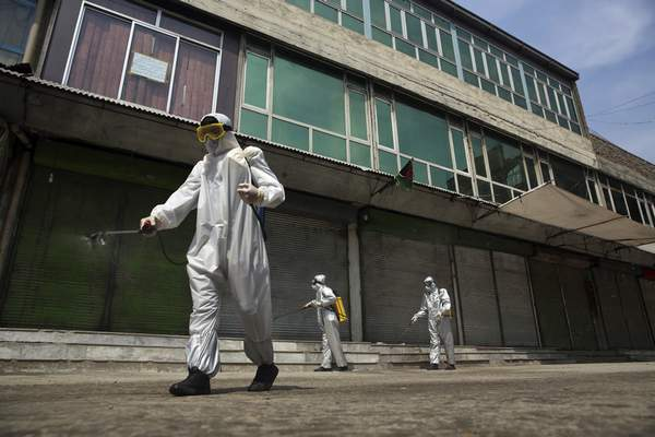 Volunteers in protective suits spray disinfectant on storefronts to help curb the spread of the coronavirus in Kabul, Afghanistan, Sunday, March 29, 2020. (AP Photo/Rahmat Gul)