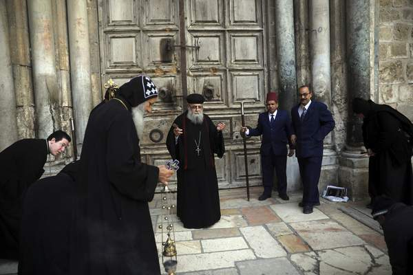 Coptic orthodox priests hold a mass outside closed Church of the Holy Sepulchre, where Christians believe Jesus Christ was buried, in Jerusalem, Saturday, March 28, 2020, as Israel tightens measures to fight the spread of the coronavirus. (AP Photo/Mahmoud Illean)