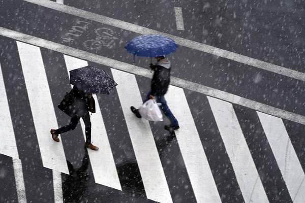 Men walk in falling snow in Tokyo Saturday, March 28, 2020. Tokyo Gov. Yuriko Koike has repeatedly asked the city's 13 million residents to stay home this weekend, saying the capital is on the brink of an explosion in virus infections. (AP Photo/Eugene Hoshiko)