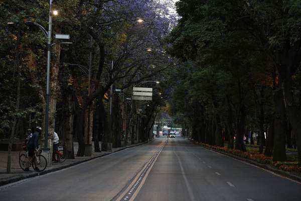 Little traffic is seen on the usually crowded Paseo de la Reforma in Mexico City, at dusk Saturday, March 28, 2020. (AP Photo/Rebecca Blackwell)