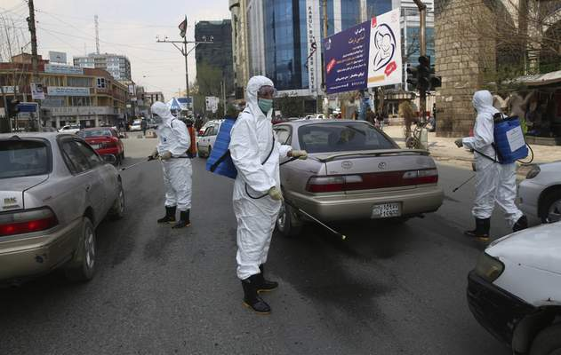 Volunteers in protective suits spray disinfectant on passing vehicles helping curb the spread of the coronavirus in Kabul, Afghanistan, Sunday, March 29, 2020. (AP Photo/Rahmat Gul)