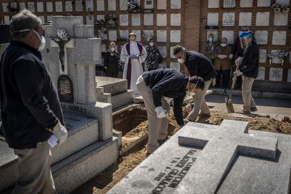 A priest and relatives pray as a victim of the COVID-19 is buried by undertakers at the Almudena cemetery in Madrid, Spain, Saturday March 28, 2020. (AP Photo/Olmo Calvo)