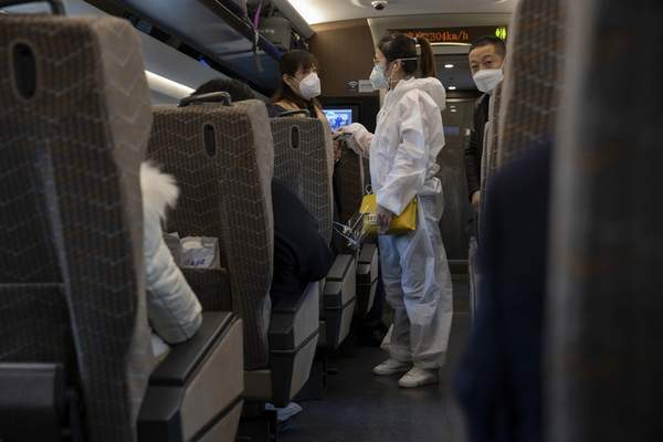 A traveler wearing a protective suit chats with another onboard a train leaving from the train station in Beijing on Sunday, March 29, 2020.  (AP Photo/Ng Han Guan)