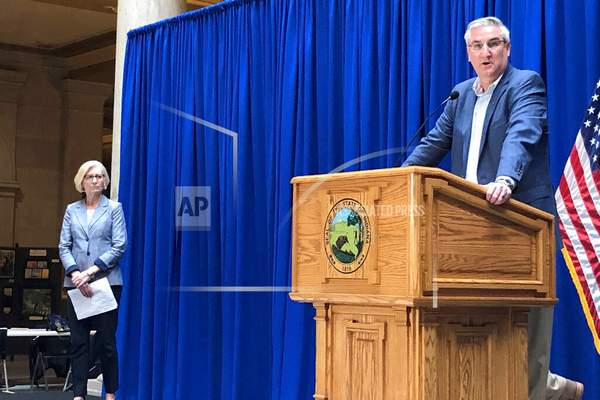 Tom Davies | Associated Press: Indiana Gov. Eric Holcomb, right, speaks during a news conference Friday at the Statehouse in Indianapolis while Dr. Kristina Box, the Indiana state health commissioner, listens.