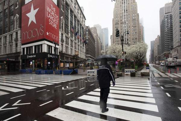 Associated Press: In this March 23 file photo, a man crosses the street in front of Macy's in New York. Macy's is furloughing most of its 130,000 workers beginning this week as its sales have collapsed because of the coronavirus pandemic.