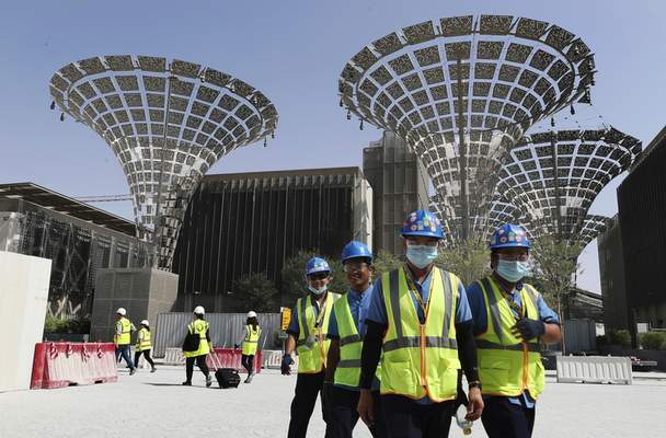 FILE - In this Oct. 8, 2019 file photo, technicians walk at the under construction site of the Expo 2020 in Dubai, United Arab Emirates. (AP Photo/Kamran Jebreili, File)