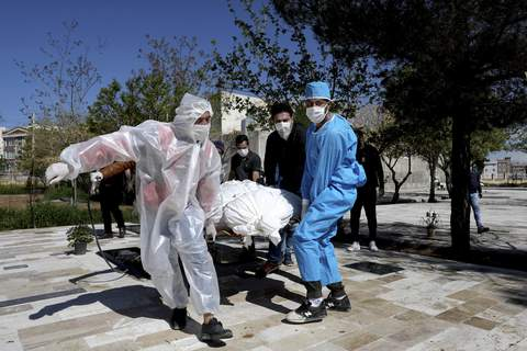 Virus Outbreak Mideast Iran People wearing protective clothing carry the body of a victim who died after being infected with the new coronavirus at a cemetery just outside Tehran, Iran, Monday, March 30, 2020. (AP Photo/Ebrahim Noroozi) (Ebrahim Noroozi STR)