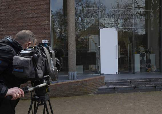 A cameraman films the glass door which was smashed during a break-in at the Singer Museum in Laren, Netherlands, Monday March 30, 2020. (AP Photo/Peter Dejong)