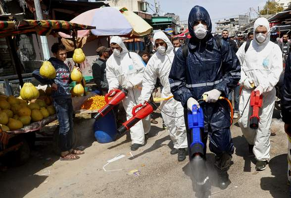 FILE - In this Thursday, March 19, 2020 file photo, workers wearing protective gear spray disinfectant as a precaution against the coronavirus, at the main market in Gaza City. (AP Photo/Adel Hana, File)