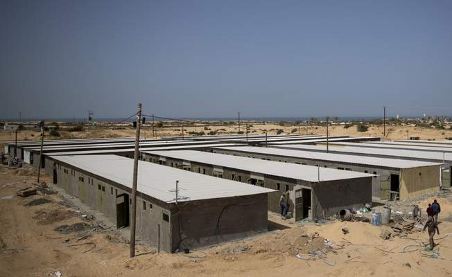 Palestinian workers construct a quarantine complex to be used for coronavirus cases, in the southern Gaza Strip, Monday, March 30, 2020. (AP Photo/Khalil Hamra)