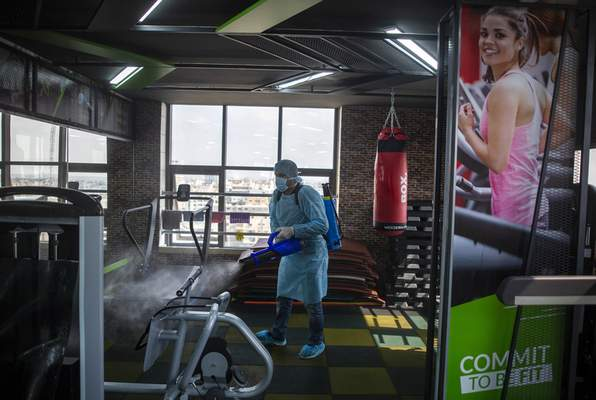 FILE - In this Sunday, March 15, 2020 file photo, A Palestinian Health worker sprays disinfectant as a precaution against the coronavirus in a gymnasium in Gaza City. (AP Photo/Khalil Hamra, File)