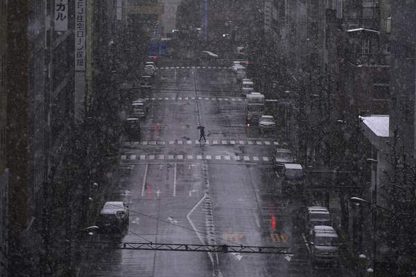 FILE - In this March 29, 2020, file, photo, a person walks in falling snow in Tokyo. (AP Photo/Eugene Hoshiko, File)