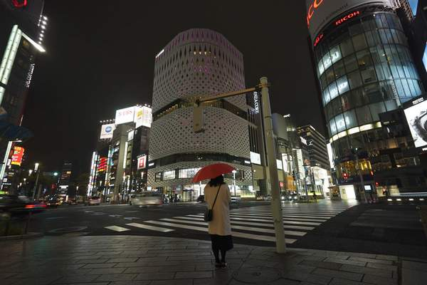 FILE - In this March 28, 2020, file, photo, a woman stands at empty Ginza shopping district in Tokyo Saturday, March 28, 2020. (AP Photo/Eugene Hoshiko, File)