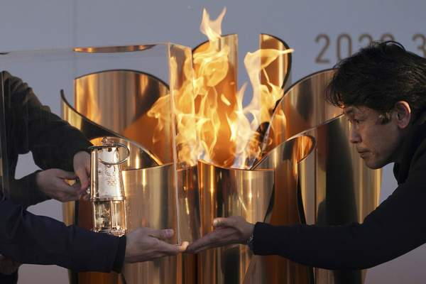 FILE - In this March 25, 2020, file, photo, officials light a lantern from the Olympic Flame at the end of a flame display ceremony in Iwaki, northern Japan. (AP Photo/Eugene Hoshiko, File)