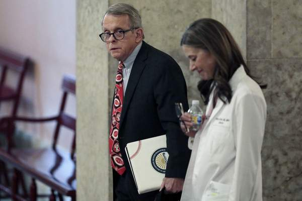 Ohio Gov. Mike DeWine, left, and Dr. Amy Acton, director of the Ohio Department of Health, leave the State Room before their daily update on the states response to the ongoing COVID-19 pandemic on Thursday, March 26, 2020 at the Ohio Statehouse in Columbus, Ohio. (Joshua A. Bickel/The Columbus Dispatch via AP)