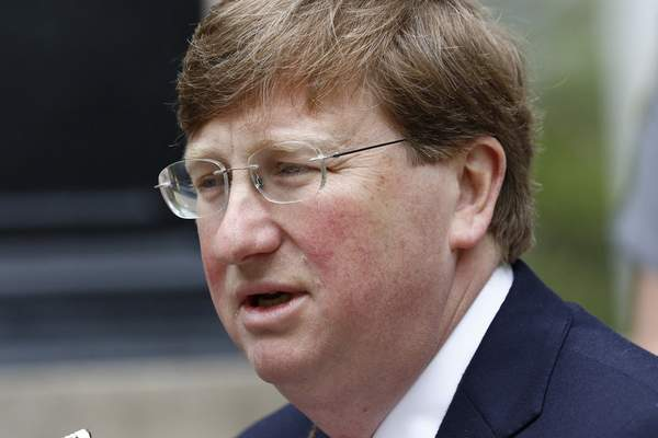 FILE - In this Tuesday, March 24, 2020, file photo, Mississippi Republican Gov. Tate Reeves speaks with reporters outside the Governor's Mansion to give an update on the current situation of the new coronavirus in the state. (AP Photo/Rogelio V. Solis, File)
