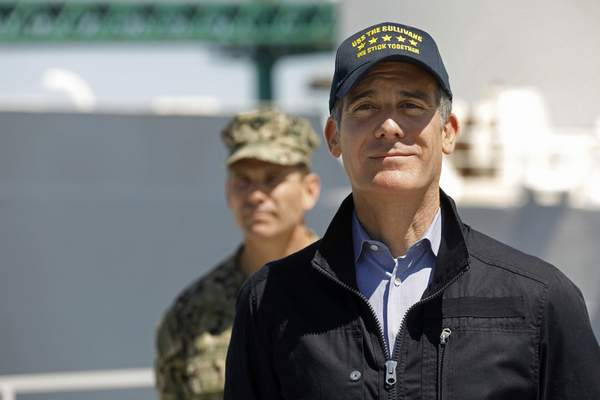Los Angeles Mayor Eric Garcetti listens as California Governor Gavin Newsom speaks in front of the hospital ship US Naval Ship Mercy that arrived into the Port of Los Angeles on Friday, March 27, 2020, to provide relief for Southland hospitals overwhelmed by the coronavirus pandemic. Admiral John Gumbleton, U.S. Navy stands behind Mayor Garcetti. (Carolyn Cole/Los Angeles Times via AP, Pool)