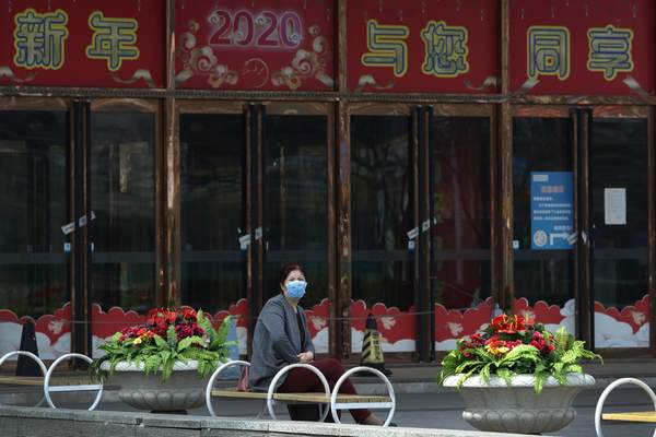 A woman wearing a protective face mask sits outside a retail and wholesale clothing mall which remain closed following the new coronavirus outbreak in Beijing, Monday, March 30, 2020. (AP Photo/Andy Wong)