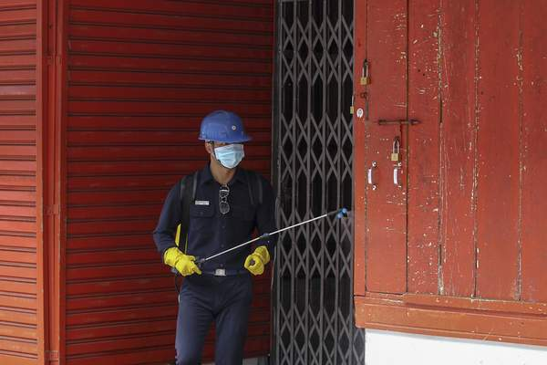 A member of Yangon City Development Committee sprays disinfectant on storefronts at the Scott market in hopes of curbing the spread of the new coronavirus in Yangon, Myanmar Monday, March 30, 2020. (AP Photo/Thein Zaw)