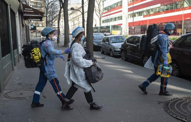 In this photo taken Saturday March 28, 2020, members of the Civil Protection service, Cyril Lamriben, right, and Noemie Biamba, left, escort to an ambulance a woman possibly infected with the Covid-19 virus in Paris. (AP Photo/Michel Euler)