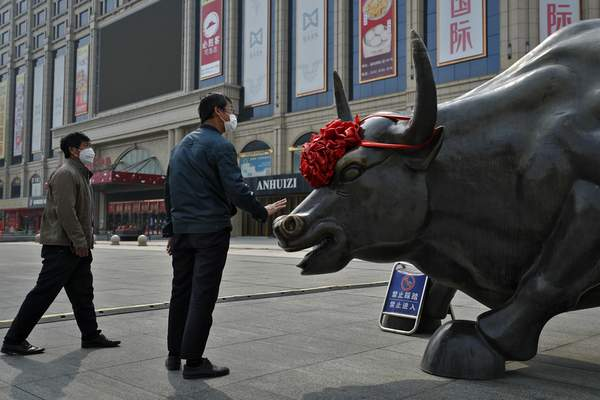 A man wearing a protective face mask touches the investment icon bull statue on display outside a retail and wholesale clothing mall which remain closed following the new coronavirus outbreak in Beijing, Monday, March 30, 2020. (AP Photo/Andy Wong)