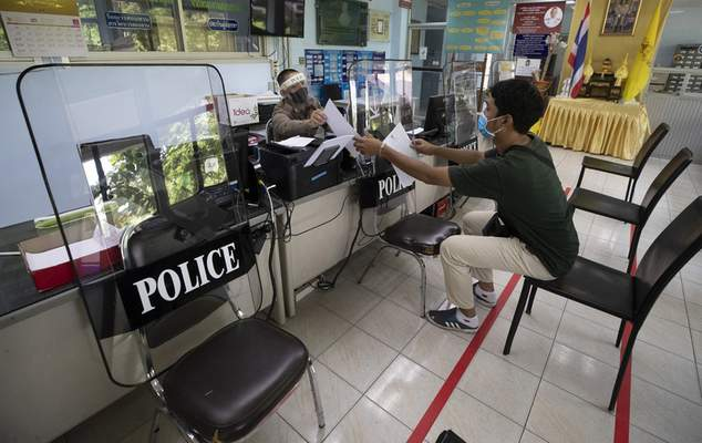 Police use riot shields to practice social distancing to help curb the spread of the coronavirus at the Tha Phra police station on Monday, March 30, 2020. (AP Photo/Sakchai Lalit)