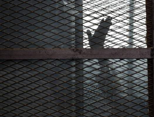 FILE - In this Aug. 22, 2015 file photo, a Muslim Brotherhood member waves his hand from a defendants cage in a courtroom in Torah prison, southern Cairo, Egypt. (AP Photo/Amr Nabil, File)